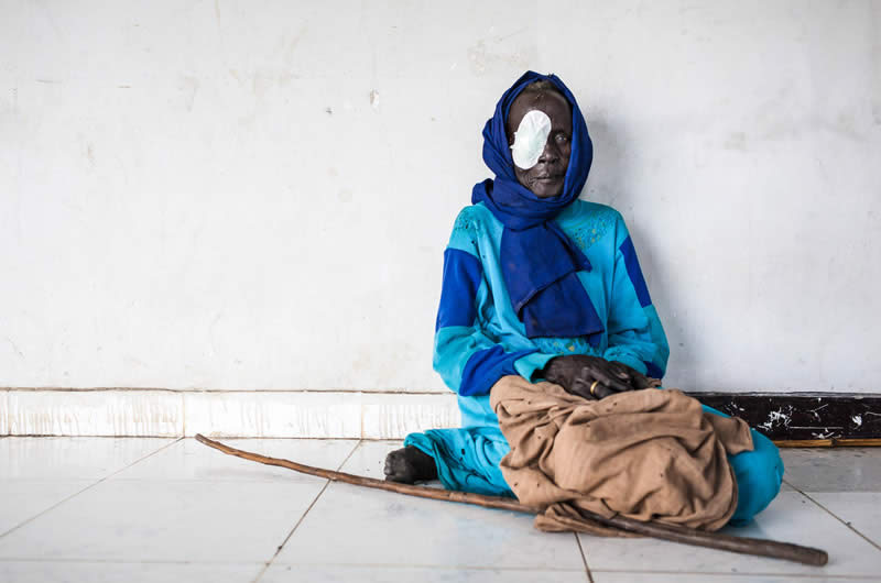 A woman rests in the hallway after her cataract operation, conducted at a clinic in South Sudan as part of an outreach programme. Adriane Ohanesian/Sightsavers