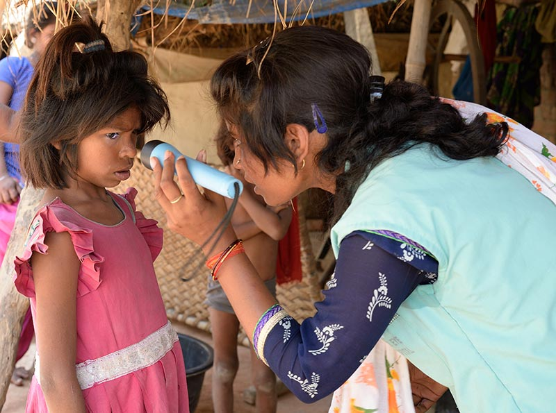Female community health worker examining a little girl's eyes using a torch