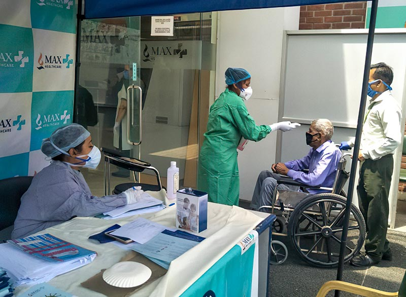 A patient in a wheelchair is being accompanied to the clinic where a female health worker checks his temperature at the entrance