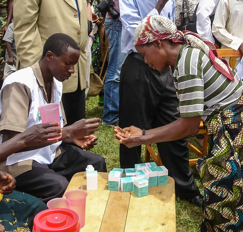 African male ivermectin administrator counting out tablets for an African lady.